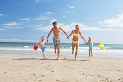 Family on beach vacation. Running away from the sea hand in hand Stock Image
