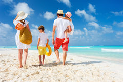 Family beach vacation. Back view of a happy family at tropical beach on summer vacation Stock Images