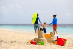 Family beach vacation concept. Sand castle and family on the beach royalty free stock photography