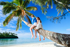 Family on beach vacation. Mother and little girl at tropical beach sitting on palm tree during summer vacation on exotic island in South Pacific stock images