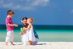Family beach vacation. Young mother with her two kids on tropical beach vacation royalty free stock photo