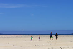 Family on Beach. White sand beach with family walking towards the sea. Suitable for background with plenty of space. People quite small and backs to the camera stock image