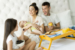 Family in bed. Family with a girl and a baby on the bed royalty free stock photography