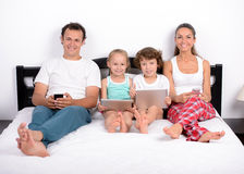 Family in bed. Modern technology in home. Young family, the use of tablets and phones, lying in bed at home royalty free stock photo