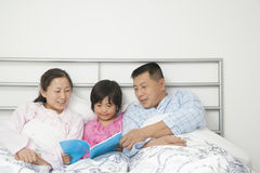 Family in Bed Reading Stock Image