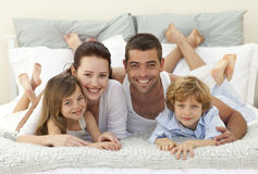 Family in bed smiling at the camera royalty free stock photo