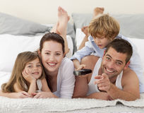Family  in bed and using a remote Stock Images