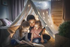 Mom and children reading book. Family bedtime. Mom and children daughters are reading a book in tent. Pretty young mother and lovely girls having fun in children Stock Images