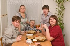 Family behind a dining table. Stock Image