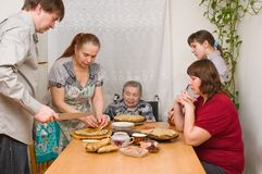 Family behind a dining table. Stock Images