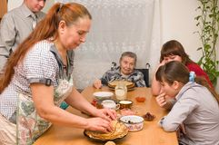 Family behind a dining table. Stock Photos