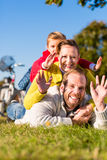 Family with bicycle in park  in fall Royalty Free Stock Photography