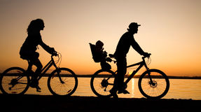 Family bicycler. Young family go for a cycle ride on the beach at background sunset Stock Photo