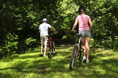 Family on bicycles. Teenage girl and her father with bicycles in summer park Royalty Free Stock Image