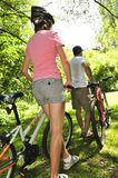 Family on bicycles. Teenage girl and her father with bicycles in summer park Royalty Free Stock Photo