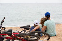 Family with bicycles on beach. Couple with teenager son with cycles behind in vacation at seaside Royalty Free Stock Images