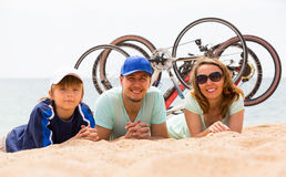 Family with bicycles on beach. Couple with teenager son lying at seashore in summer day with cycles behind Royalty Free Stock Photo