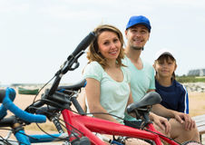 Family with bicycles on beach. Couple with teenager son sitting at seashore in summer day with cycles Stock Image