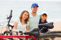 Family with bicycles on beach. Family with teenager son sitting at seashore in summer day with cycles Royalty Free Stock Photo