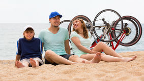 Family with bicycles on beach. Family with teenager son sitting at seashore in summer day with cycles behind Stock Photography
