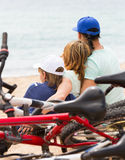 Family with bicycles on beach. Family of three with bicycles behind in vacation at seashore Stock Image