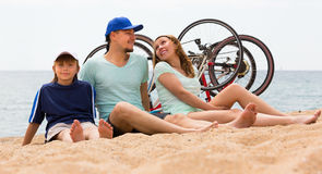 Family with bicycles on beach. Family of three with cycles behind at seashore in summer day Royalty Free Stock Image