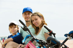 Family with bicycles on beach. Family of three with cycles behind at seaside in summer day Stock Image