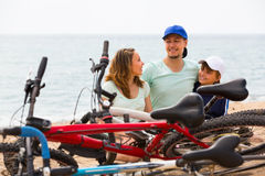 Family with bicycles on beach. Family of three with cycles behind in vacation at seaside Royalty Free Stock Photo