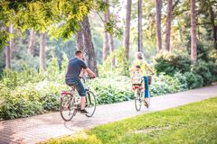 Family on bicycles in park- little Boy on bike with mother and father. Happy family on bicycles in park- little Boy on bike with mother and father stock photos