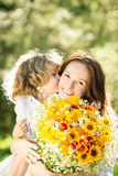 Woman and child with bouquet of flowers. Family with big bouquet of spring flowers. Child kissing woman. Mothers day concept Stock Photography
