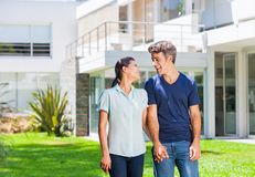 Family in big house. Happy couple family near new house, men and women outdoor holding hands looking to each other smile concept of real estate stock images