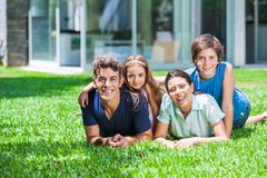 Family in big house. Happy family lying  on grass in front of house, parents with two children smile Royalty Free Stock Image