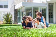 Family in big house. Happy family lying on grass in front of house, parents with two children smile stock photos
