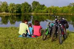 Family bike ride outdoors, active parents and kid cycling. And relaxing near beautiful river Stock Photography