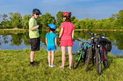 Family bike ride outdoors, active parents and kid cycling Stock Photos