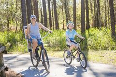 Family on a bike ride together outdoors on a sunny day Stock Photo
