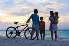 Family with a bike at tropical beach Royalty Free Stock Images