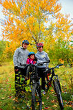 Family on bikes in autumn park, parents and kid cycling Stock Images