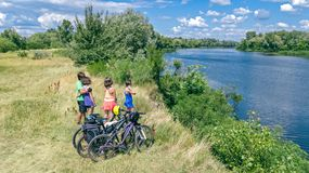 Family on bikes cycling outdoors, active parents and kids on bicycles, aerial view of happy family with children relaxing. Near beautiful river from above royalty free stock photos