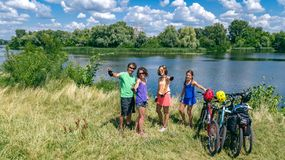 Family on bikes cycling outdoors, active parents and kids on bicycles, aerial view of happy family with children relaxing. Near beautiful river from above royalty free stock photography