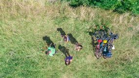 Family on bikes cycling outdoors, active parents and kids on bicycles, aerial view of happy family with children relaxing. Near beautiful river from above stock photography