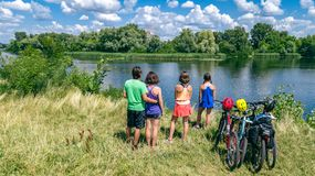 Family on bikes cycling outdoors, active parents and kids on bicycles, aerial view of happy family with children relaxing. Near beautiful river from above royalty free stock images