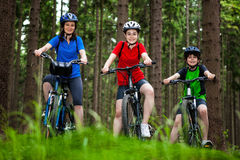 Family biking. Mother and kids biking in forest Stock Photography