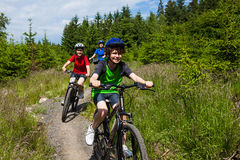 Family biking. Mother and kids biking in forest Royalty Free Stock Image