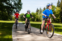 Family biking. Mother and kids biking in park Stock Photos