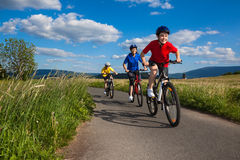 Family biking. Active people - mother and kids biking Royalty Free Stock Photography