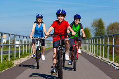 Family biking. Active people - mother and kids biking Stock Image