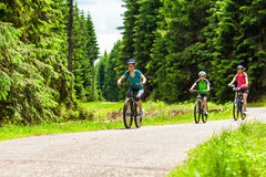 Family biking. Mother and kids biking in forest Stock Image