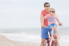 Family biking at the beach. Family of father and son enjoying riding bicycle together at the beach Stock Photo