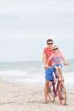 Family biking at the beach. Happy family of father and son enjoying their time together while biking at the beach Royalty Free Stock Photo